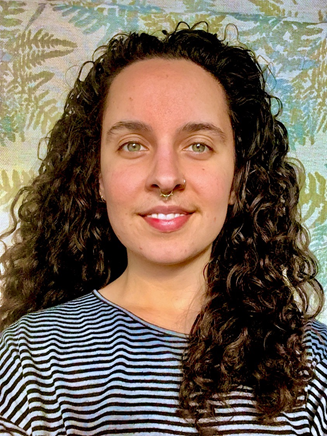 Artist Alia Jeraj in front of a flowery background with dark curly hair and a nose ring.