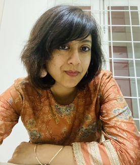 Artist Ritika Ganguly leaning towards the camera wearing an ornate Indian shirt with earrings and bracelets.