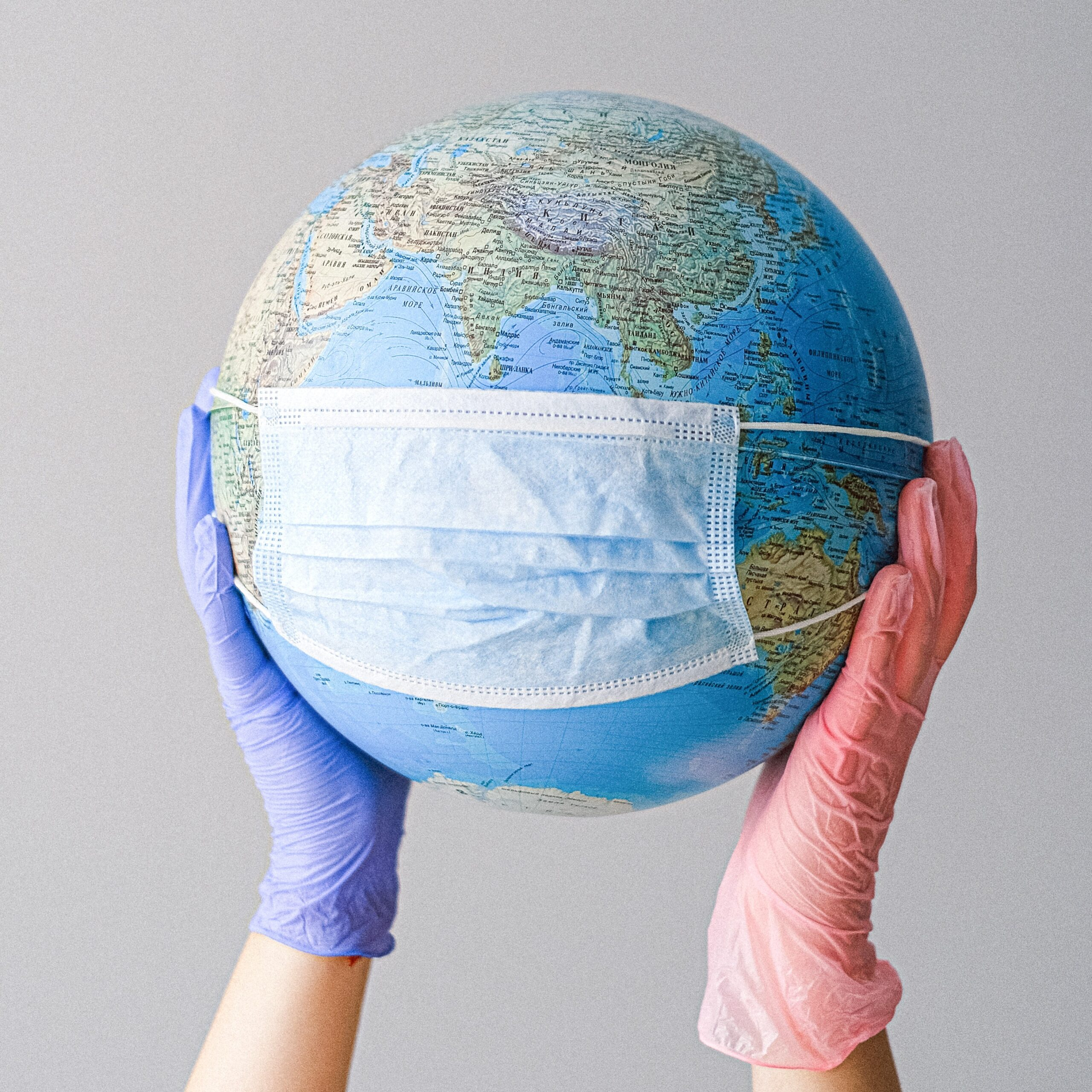 Gloved hands holding up a globe with a face mask on it.