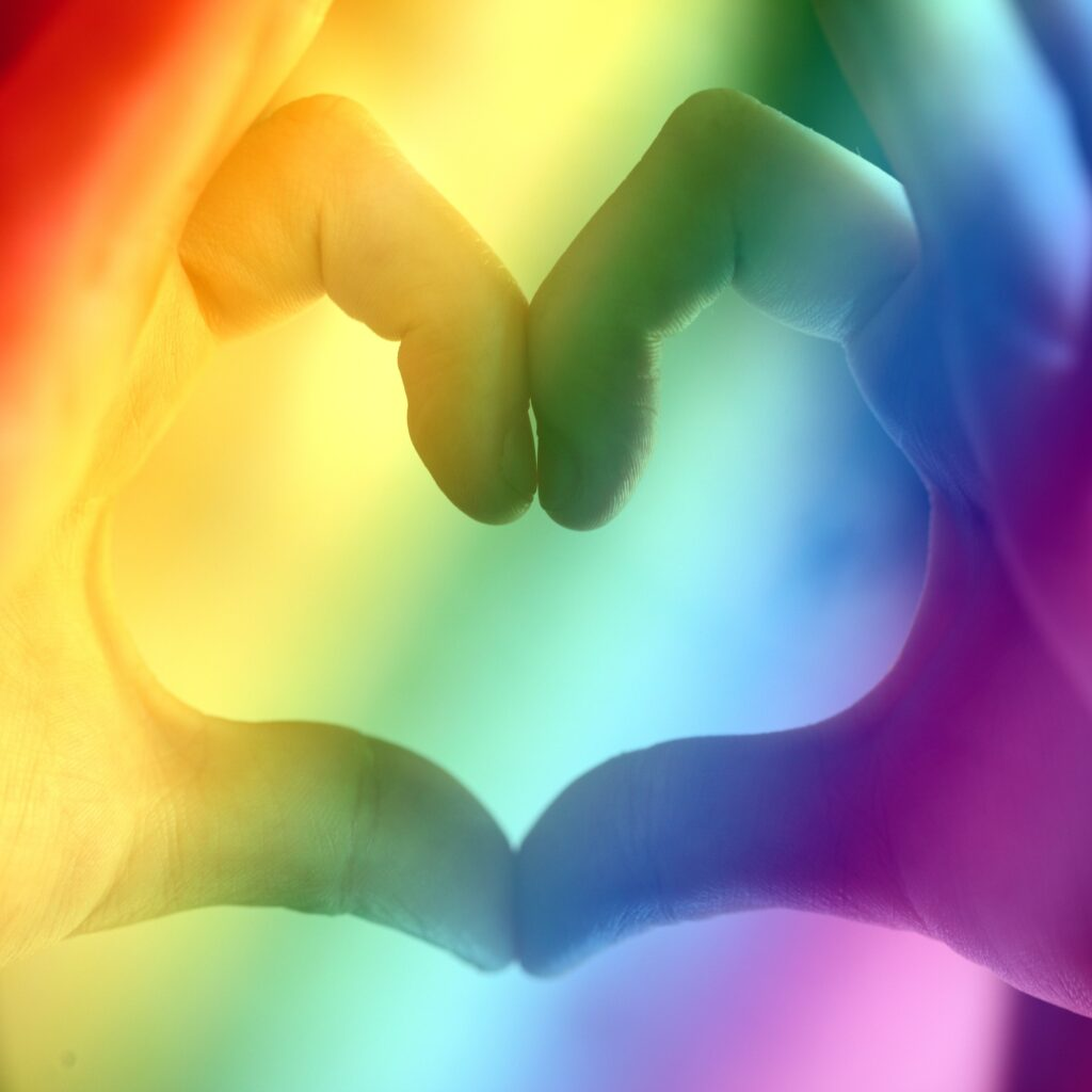 Image of a person's thumbs and index fingers making a heart with a pride rainbow overlaid.
