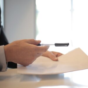 Image of hands holding a pen and paper.