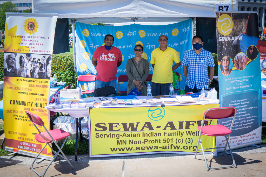 SEWA-AIFW staff and volunteers at SEWA's booth on the capitol grounds.