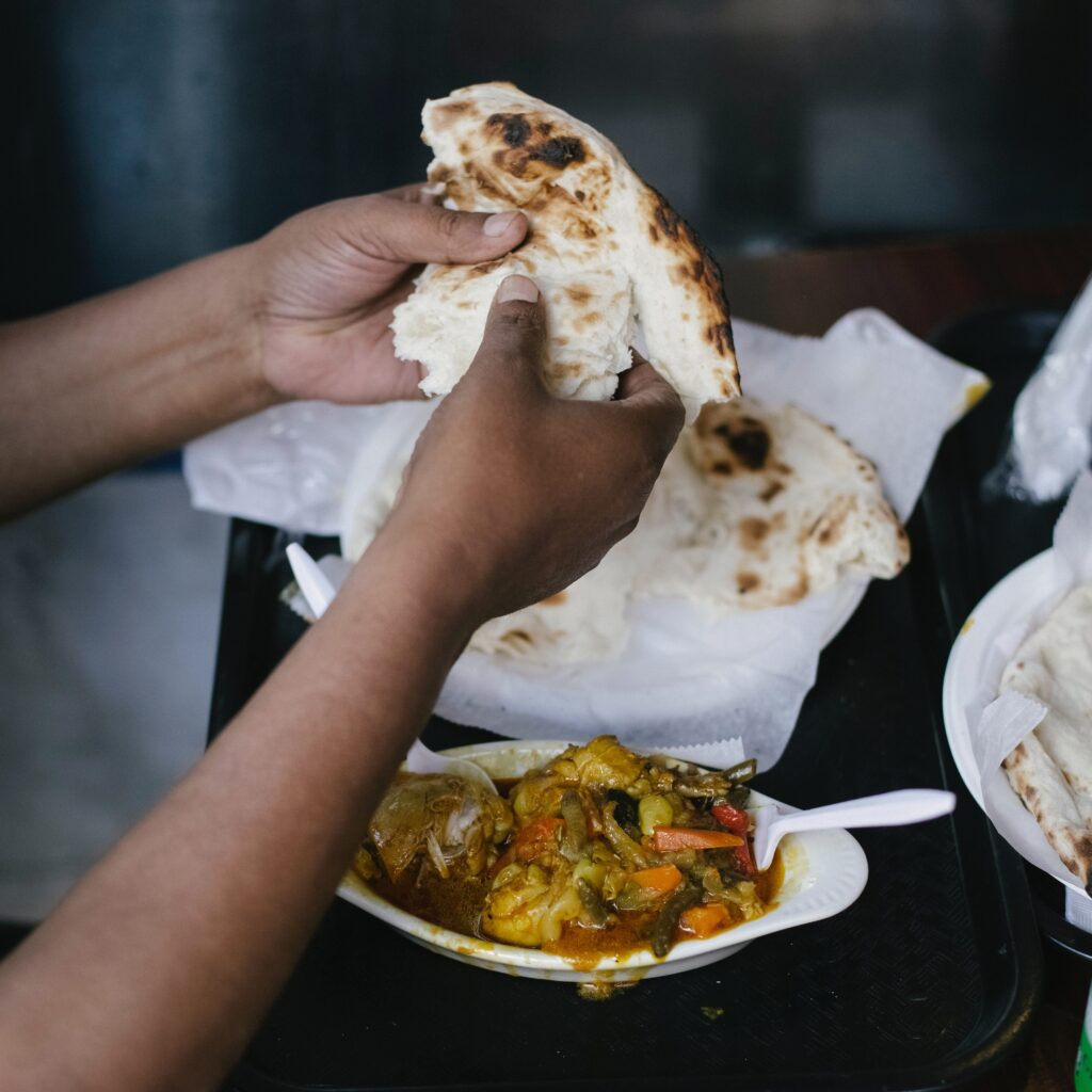 Image description: A pair of hands tearing a piece of naan over a curry dish.
